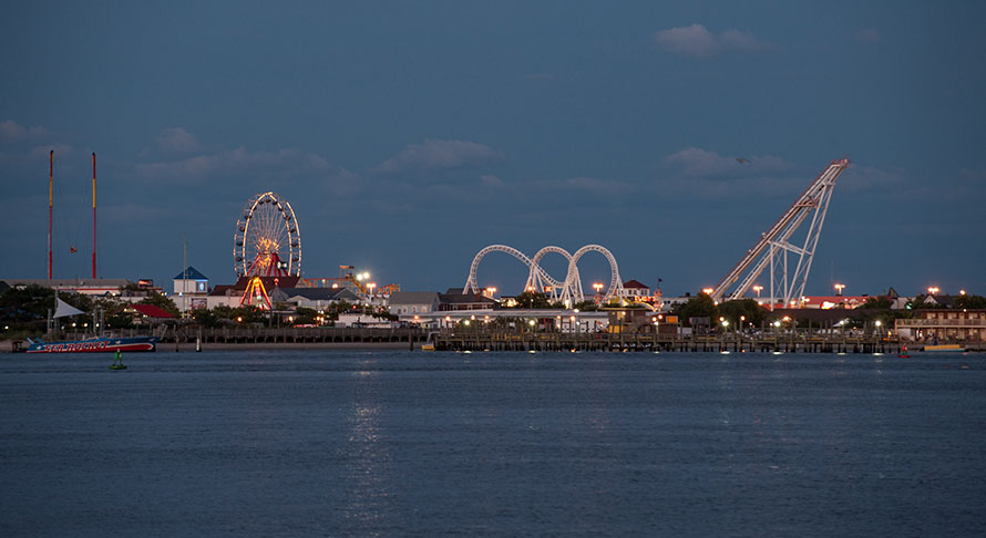 Wide bay view of boardwalk and tall amusement rides lit up at dusk
