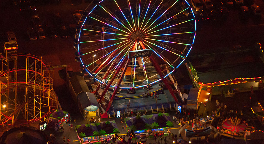 Aerial view of inlet pier amusment park and iferris wheel colorfully lit at night