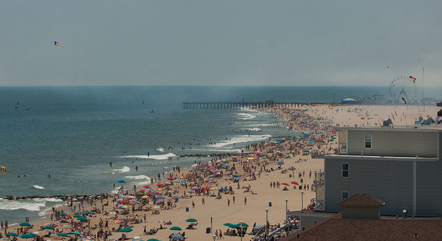 Aeriel view of crowded Ocean City beach, boardwalk, and inlet pier and amusements