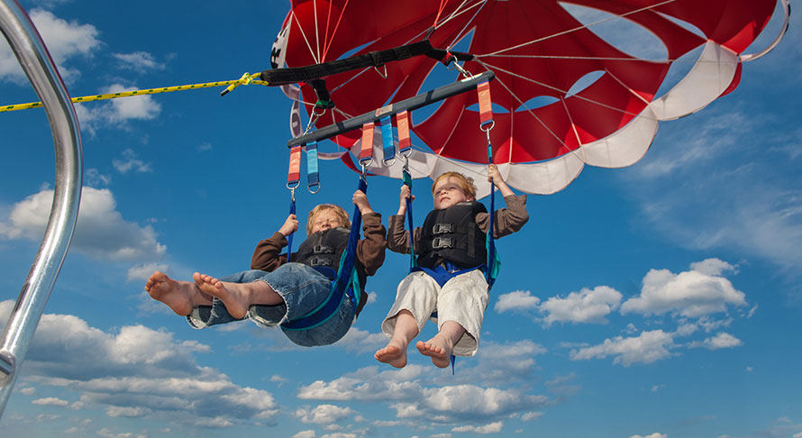 2 young boys parasailing into the partly cloudy blue sky