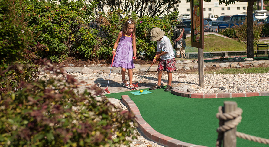 Boy and girl teeing up at miniature golf course
