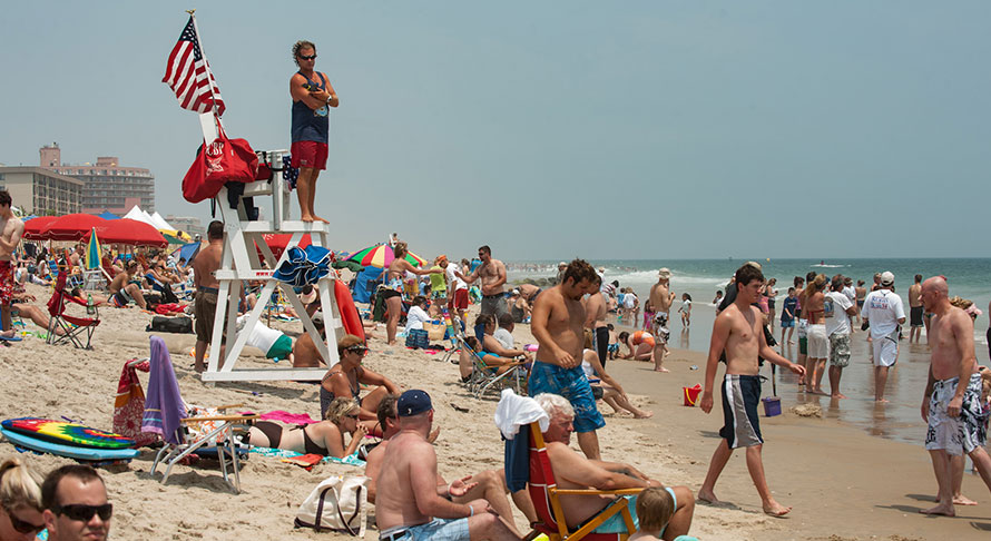Lifeguard standing on his station overlooking crowed Ocean City beach