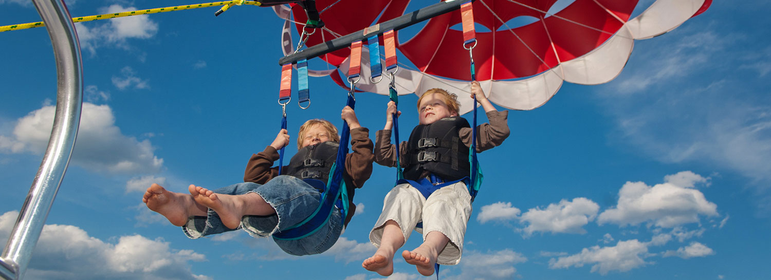 2 smiling young boys sitting tandem in parasail harness lifting into the sky